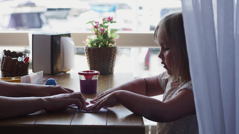 Mother show little girl make paper ship on terrace of restaurant at table Live Action
