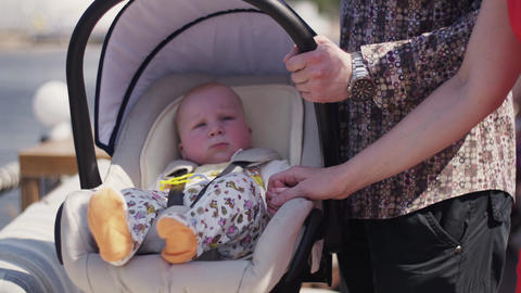 Parents stay on street with cute baby in baby carriage. Family. Happiness Footage