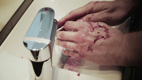 Man cleans his hands covered in blood Footage