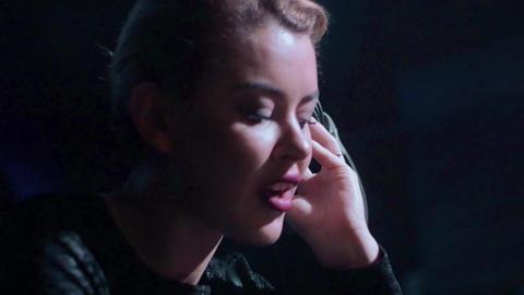 Attractive Dj girl in black top mixing at turntable in nightclub. Headphones Footage