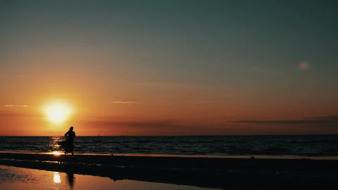 Silhouette of girl in dress running on beach. Red sunset. Model. Waves Footage