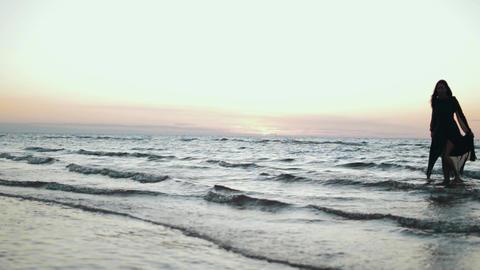 Girl in dark dress running on water on coast. Photoshoot. Splash. Model. Sea Footage