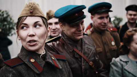 Woman and group of men in old soldiers soviet uniform jocking an Live Action