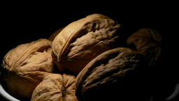 Walnuts in a white bowl gyrating on black background with a cenital light Footage