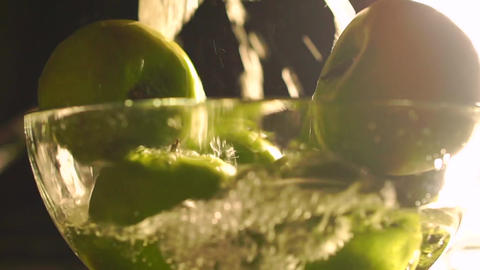 Washing green apples in a glass bowl, slow motion video Footage