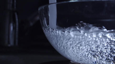Water from water tap filling and overflowing a glass bowl, slow motion video Footage
