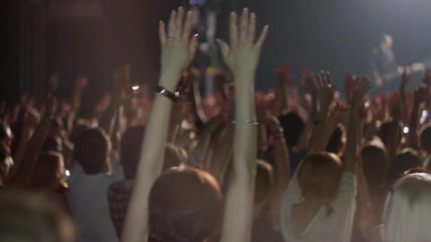 Crowd of people raise hands on rock concert in nightclub. Band performing on Footage