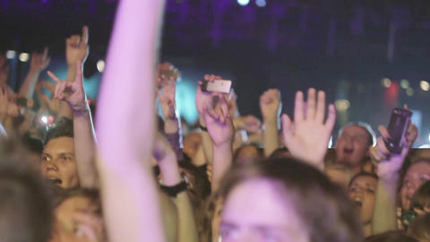 People raise hands on live rock concert in nightclub. Show two fingers ビデオ