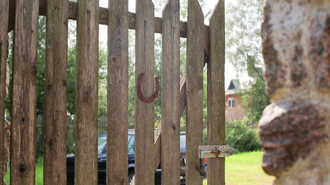 Gate with rusty horseshoe. Green courtyard, car background. Countryside. Nobody Live Action