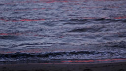 Sea waves gently wash up after red sunset. Slow motion. Nobody Live Action