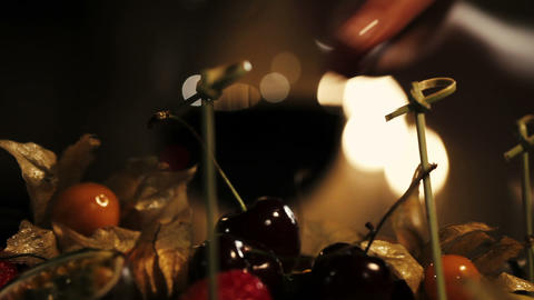 Woman take cherry from plate with fruits in restaurant. Dinner. Romantic Live Action