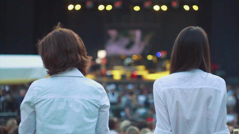 Back side of two girls in blue shirts at summer live concert. Music band Footage