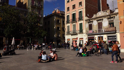 Small Barcelona square at sunny february weekend, Citizens rest, panning shot Footage