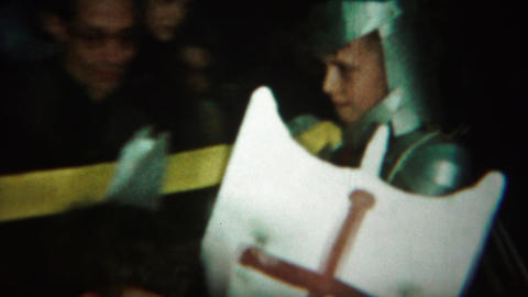 1964: Boy wearing knight costume crowd watching walk down aisle Footage