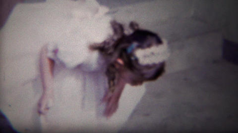 1954: Girl looking for Easter eggs leaves home in white fancy dress Footage
