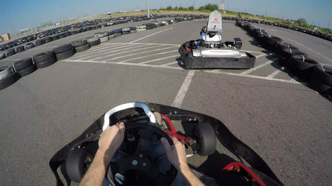 two drivers drive go kart and overtaking on outdoor track, camera is attached to Live Action