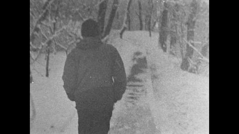 a man in a tracksuit goes through winter forest ( shot on 16 mm film) Footage