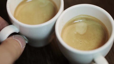 Two cups of fresh cooked coffee. Man hand straightens one cup Live Action