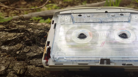 Audio cassette playing. Audio player lies on the bark of a tree and wind a of an Footage