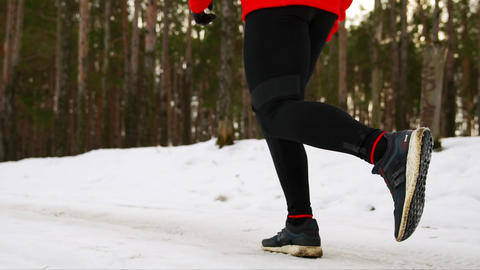 Close-up of foot running in winter on snow in sneakers through the forest. Slow Footage