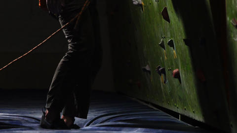 Close-up a male climber begins climbing the wall of the climbing wall with Footage