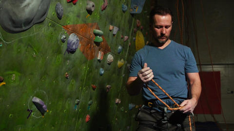 A climber man prepares the equipment against the backdrop of a climbing wall Footage