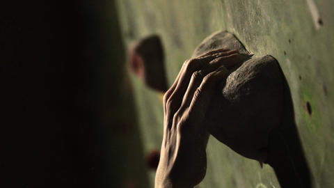 Close-up of a climber climbs on a stone wall indoors. The... Stock Video Footage