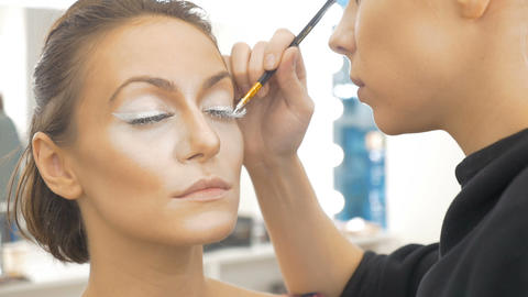 Professional make-up artist, paints special white paint, model eyelashes Footage