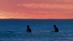 Two Surfers On Their Boards Waiting For A Wave At Sunset Footage