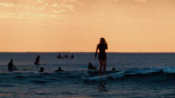 Silhouettes of Surfers Surfing at Sunset 画像
