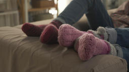 Wan's pair of legs lies on the couch in woolen socks, near plan, comfort. 60 fps Footage