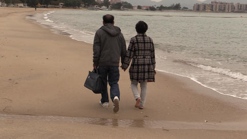 couple walking on the beach Footage