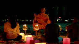 Buddhist Monk Sharing On A Beach At Night GIF