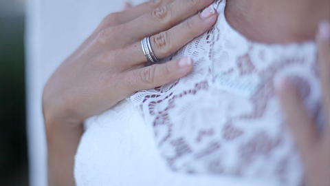 girl with a neat manicure in a white dress adjusts the chain Footage