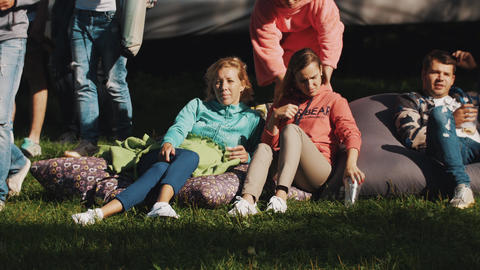 Young woman lying on bean bags, relaxing in the park during the open event Footage