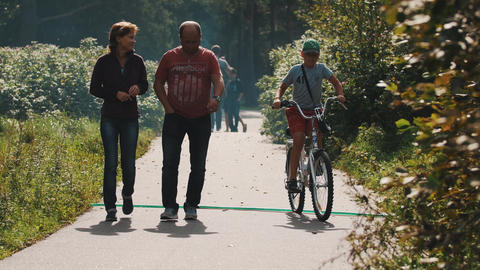 Couple walks along road in park. Man smoking. Boy on a bicycle passing by Footage