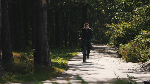 Boy rides a bicycle toward camera along a road in a forest and leaves shot Footage