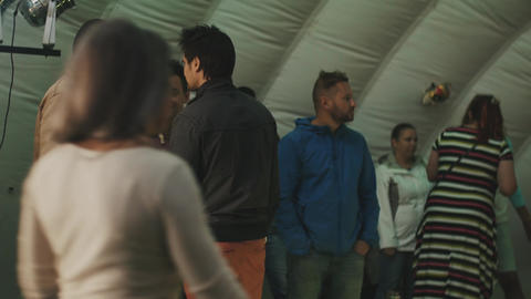 Young people stand inside of a tent. talking. Changing colorful lights Footage