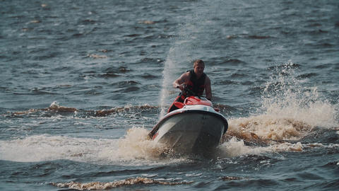 Fat guy in life vest riding jet ski on lake water, making twists and jumps Footage