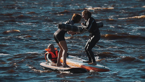 Two women in life vests fighting with soft bats surfing boards in water Footage