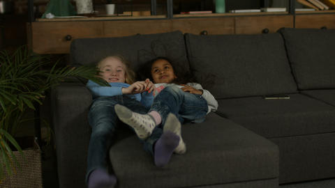 Two multiracial little girls playing on the couch Footage