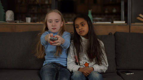 Little girls on the couch switch TV channels Footage