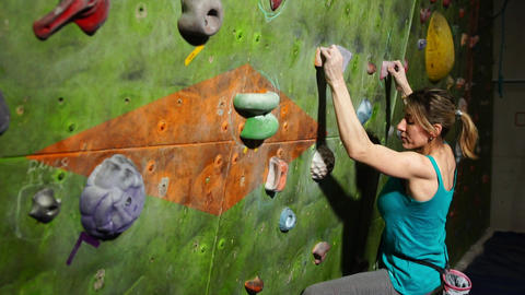 A female boulder trains to overcome obstacles on the wall for climbers Footage