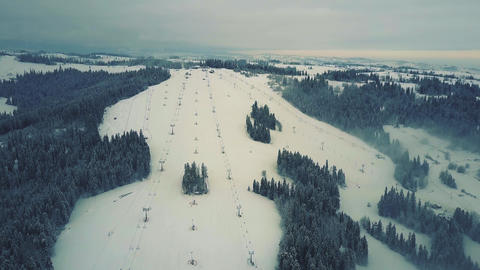 Aerial shot of mountain ski slopes and lifts in the snow Footage