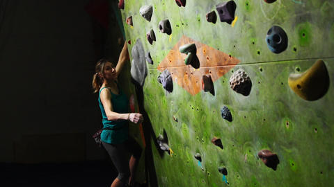 A woman climber is trained to overcome obstacles on the wall for rock climbers Live Action