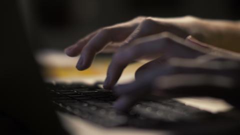 Female hands typing on keyboard on modern laptop computer in dark interior Footage