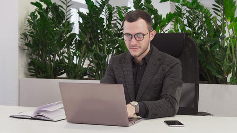 Young business man in suit working on laptop Live Action