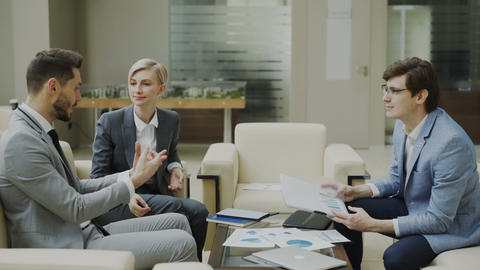 Businessman discussing financial reports with female and male business partners Footage