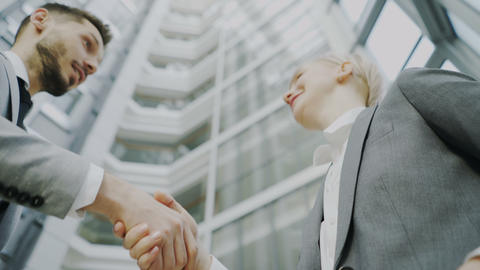 Low angle shot of bearded businessman shaking hands and talking with female Footage