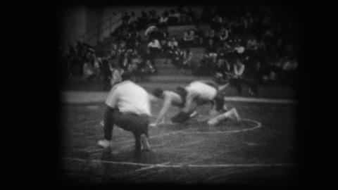 Archival footage of two young men wrestling near an official Footage